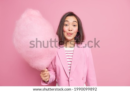 Good looking brunette Asian woman licks lips as holds appetizing sweet candy floss dressed in fashionable formal outfit isolated over pink background. Teenage girl with delicious cotton candy Royalty-Free Stock Photo #1990099892