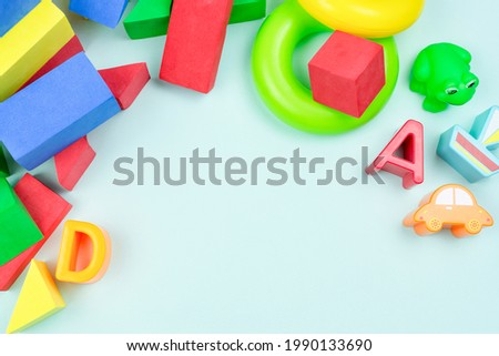 Children's background, frame. Multi-colored soft constructor, figures of a boat, cars, letters, a pyramid on a blue background. Space for the text. Development of the child's motor skills.