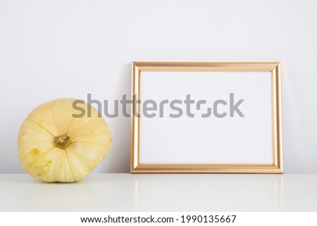 Autumn frame, background. Thanksgiving mockup with golden frame and yellow pumpkin. Halloween, fall minimal composition with copy space.