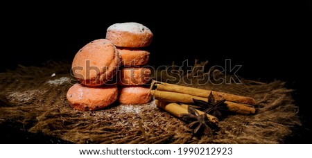 Closeup of Fresh Homebaked Sesame Biscuits or Cookies flavoured with Cinnamon roll and clove in a isolated rustic background with selective focus and copy space for inscription. Food photography. Royalty-Free Stock Photo #1990212923
