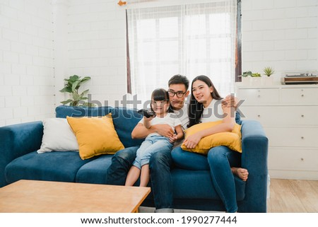 Happy Asian family enjoy their free time relax together at home. Lifestyle Korean dad, mom and daughter watching TV together and having fun lying on sofa in living room in modern house.