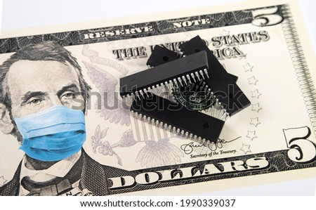 Microchips shortage in the United States because of COVID-19 pandemic. Concept. Picture of computer chips placed on banknote with applied anti virus face mask (applied by digital montage).