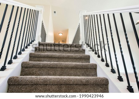 Staircase inside a house with fully carpeted steps. Fully carpeted stairs with white wooden handrailings and metal baluster leading upstairs with warm lightning at the ceiling. Royalty-Free Stock Photo #1990423946