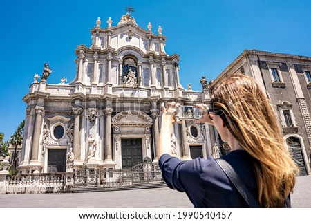 Catania, Sicily, Piazza del Duomo with Duomo of Saint Agatha, woman tourist takes a picture with smartphone on a sunny day