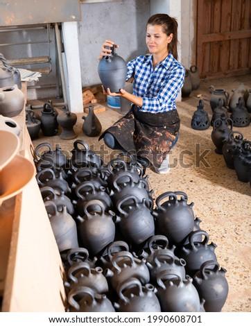 Female artisan in apron having ceramics in stock. High quality photo