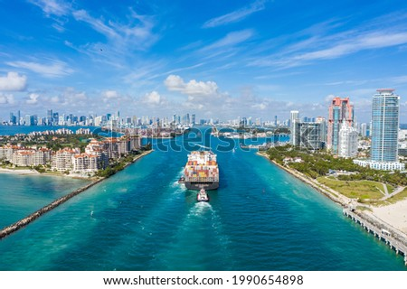 Large Container Ship Entering Harbor and Miami City on Sunny Day, USA. Aerial View.