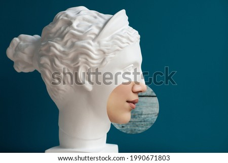 Contemporary collage of plaster statue head and woman in profile over deep blue background. Antiquity and modernity.  Royalty-Free Stock Photo #1990671803