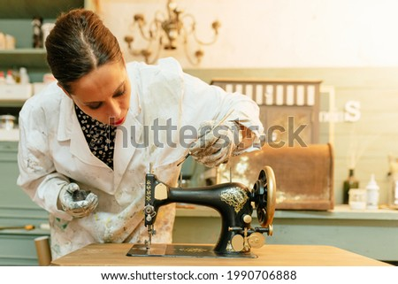 young Hispanic woman working in her carpentry shop. person restoring and painting old sewing machine. craftswoman.