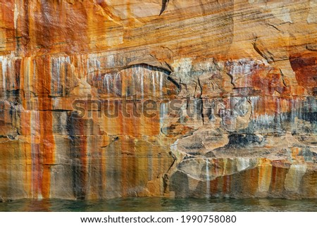 Landscape of mineral stained cliff along the eroded sandstone shoreline of Lake Superior, Pictured Rocks National Lakeshore, Michigan's Upper Peninsula, USA