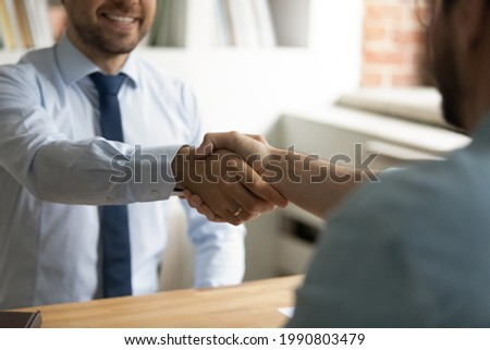 Close up happy two business men shaking hands, coming to agreement after negotiations meeting. Smiling employer welcoming job applicant at interview in office, making offer, recruitment concept. Royalty-Free Stock Photo #1990803479