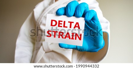 COVID-19 delta indian strain symbol. A young strong man in a white kimono for sambo, jiu jitsu and other martial arts, blue medical gloves. White card with words 'delta strain'. Delta strain concept.