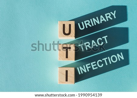 Wooden cubes building word UTI - (abbreviation Urinary Tract Infection) on light blue background. Royalty-Free Stock Photo #1990954139