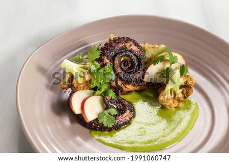 Octopus dish was named as ocean on plate, with corriander sauce, charred cauliflower flowers and fresh green apple. Beautiful art food, white background