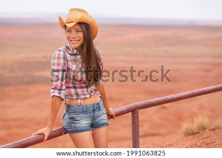 Cowgirl woman smiling happy on country farm landscape wearing cowboy hat and western shirt and jeans shorts. Young multiracial Asian American girl in desert countryside.