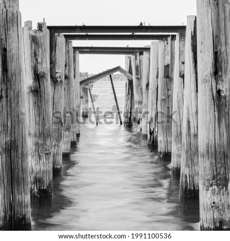 A grayscale of weathered columns of a wooden pier in the sea on background of the sky Royalty-Free Stock Photo #1991100536