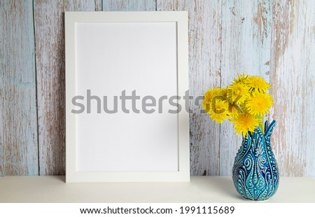Dandelion bouquet in a vase and picture frame with copy space for mockup. High quality photo