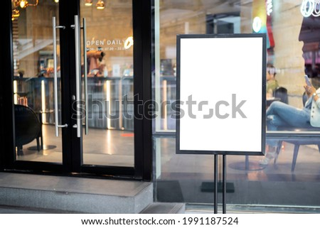mockup white poster with black frame stand in front of blur restaurant cafe background for show or present promotion product concept