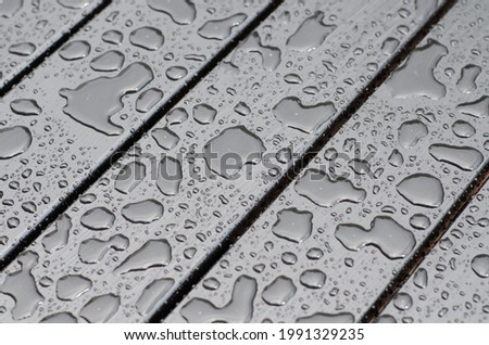 Raindrops on the surface. Water on the surface. After the rain. Water drops. Wooden boards. Royalty-Free Stock Photo #1991329235