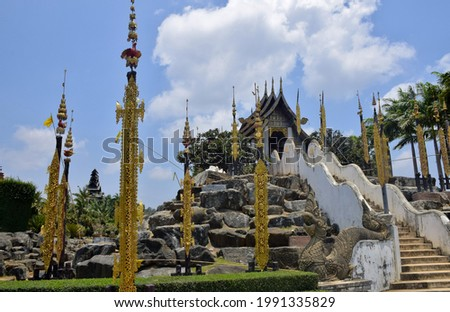 Tung Lanna, golden hanging flag in front of stairs to Hall of Kham Luang, Thai Lanna architecture temple with blue sky, Nongnooch Pattaya, Thailand