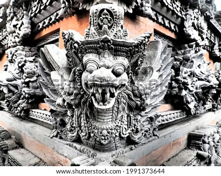 Close up picture of Garuda bird and other typical Balinese stone sculptures engraved on a wall of the side of the temple in Ubud on Bali island, Indonesia