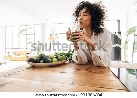 Young african american woman drinking green juice with reusable bamboo straw in loft apartment. Home concept. Healthy lifestyle concept. Copy space Royalty-Free Stock Photo #1991386604