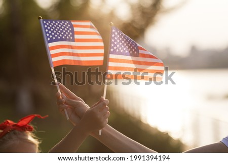 Patriotic holiday. Happy family, mother and daughter with American flag outdoors on sunset. USA celebrate independence day 4th of July. Royalty-Free Stock Photo #1991394194