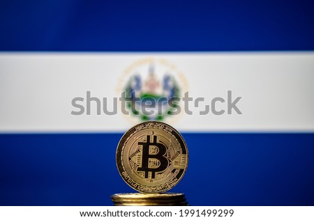 Bitcoin representation coin placed in front of blurred Salvador's national flag. El Salvador is the first country to adopt bitcoin as legal tender. Concept. Royalty-Free Stock Photo #1991499299