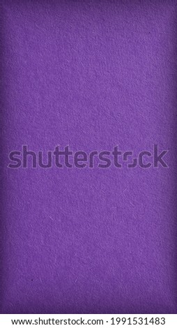 The surface of violet cardboard. Paper texture with cellulose fibers. Dark mobile phone wallpaper with vignetting. Bright purple vertical background. Saturated color. Top-down. Macro