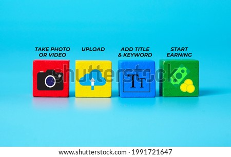 A picture of camera, upload, add title and earn money icon on wooden block. Be a stock photo and video contributor.