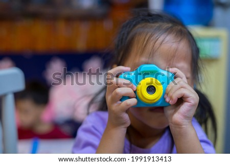 taking pictures of others. Little girl taking picture using toy camera, Photography courses. Camera in hand