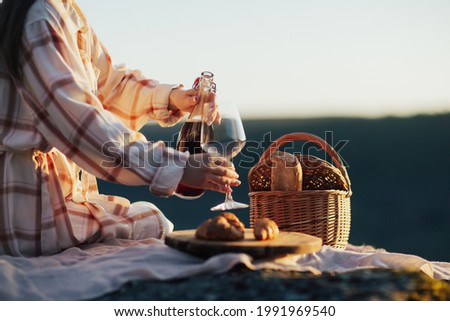 Cropped picture of a woman pouring wine while sitting at picnic. Concept of having picnic during summer holidays or weekends.