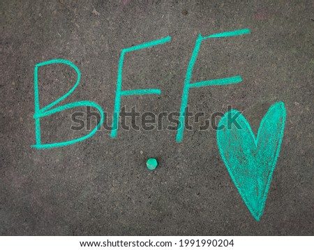 The inscription text on the grey board, BFF (Best friend forever) with hand drawn green color love symbol. Using color chalk pieces.