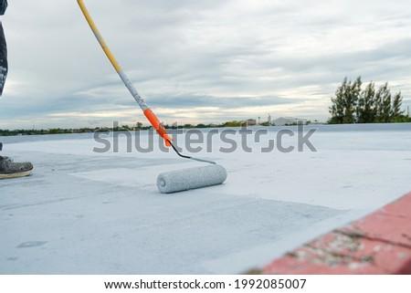 Hand painted gray flooring with paint rollers for waterproof, reinforcing net,Repairing waterproofing deck flooring. Royalty-Free Stock Photo #1992085007
