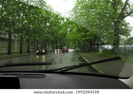 Blurred view of road through wet car window. Rainy weather Royalty-Free Stock Photo #1992094598