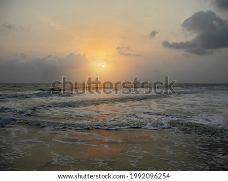 Sunset on the background of the dark gray foaming waves of the Arabian Sea. India, Kerala, Cochin. Travel concept Royalty-Free Stock Photo #1992096254