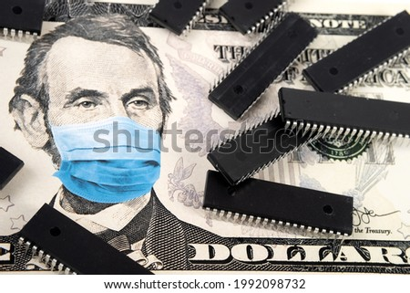 Microchips shortage in the United States because of COVID-19 pandemic. Concept. Picture of computer chips placed on 5 dollar banknote with applied anti virus face mask (printed digital montage).