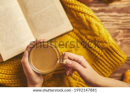 Mug of coffee, cozy knitted jacket, and open book on wooden board. Autumn still life, vintage style. Flat lay of autumn composition. Fragrant coffee in women's hands and book of stories. Royalty-Free Stock Photo #1992147881
