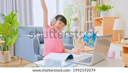 asian girl is using protractor and learning math online through laptop with headset in living room while local authority has announced a stay at home order