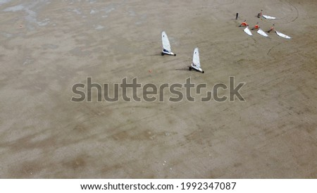 Aerial picture of land sailing also known as sand yachting or dirtboating is the act of moving across ground in a wheeled vehicle powered by wind through the use of a sail
