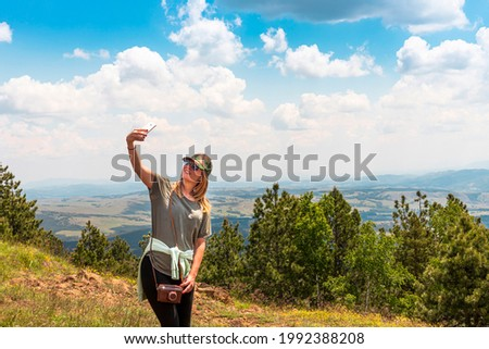Tourist girl taking selfie with smartphone while Hiking in nature at the top of the mountain