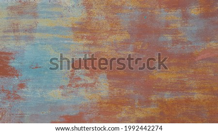 Old rusty iron texture with different layers of cracked paint. Abstract metal shabby background with copy space Royalty-Free Stock Photo #1992442274