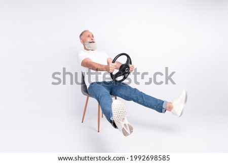 Full body photo of amazed excited old man sit chair hold wheel license test speed isolated on grey color background