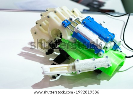 Hand prosthesis made of metal and plastic. Medical equipment for restoration of hands after accidents. Apparatus for hand and wrist joint. Apparatus for developing or repairing a brush. Royalty-Free Stock Photo #1992819386