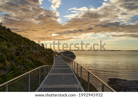 """The walkway on the coastline of """"The Atlantic Ocean Road"""" at scenic sunset Royalty-Free Stock Photo #1992945932"""