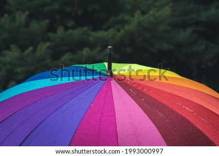 Raindrops fall from the sky onto a rainbow-colored umbrella. Light rain. Cloudy weather. Royalty-Free Stock Photo #1993000997