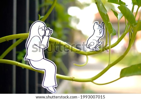 white paper artwork of a girl climbing a kale tree to take picture of her cat pet