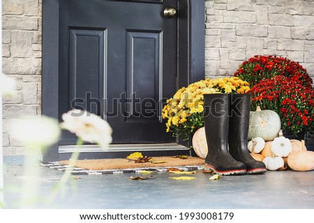 Rain boots sitting on door mat of front porch that has been decorated for autumn with heirloom white, orange and grey pumpkins and mums. Selective focus with blurred foreground and background.