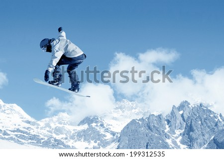 Snowboarder making jump high in clear sky #199312535