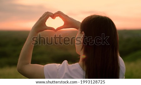 Carefree chewing girl making heart shape with her fingers. Light of summer spring sun on hands. Travel and relax in nature. Girl made love heart out of her palms. Young Woman enjoying summer, relaxing