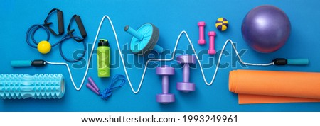still life of group sports equipment for womens and cardiogram of jump rope, on blue background. Fitness and healthy living, wellness concept. Royalty-Free Stock Photo #1993249961